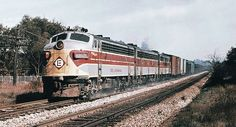 Erie Lackawanna EMD F7A diesel electric locomotive # 6321, is seen leading two other F units while hauling a mixed merchandise freight train along the mainline at Kent, Ohio, October 1969