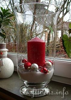 Christmas Hurricane Glass Centerpiece, with bag of fake snow, small ornaments and silver garland around the candle