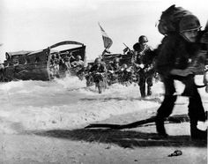 May 1944: The first wave of U.S. Infantrymen leave their higgins boats and race through the surf for the beach during the invasion of Wakde Island, Dutch New Guinea during World War II.  Note the lone grenade in foreground.