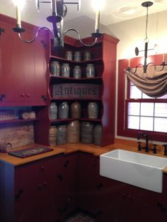 FARMHOUSE – INTERIOR – a primitive kitchen with a deep red color.