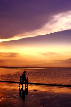 Silhouette of People Walking on Seashore Under Gray and White Clouds during Daytime