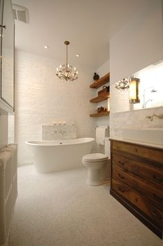 white bathroom with touches of wood. antique dresser topped with modern sink                                                                                                                                                                                 More