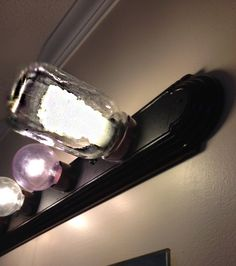 Inexpensive & Super-Easy Bathroom Mirror Light Update - DIY Edison CFL - Got old hollywood-style bathroom make-up lights? - Paint silver or brass base with any Rustoleum Metallic Paint you like - Cut a hold with wire cutters in Mason Jar Lid and put over socket - Screw in CFL bulb - Screw on Mason Jar Now you have Industrial Vintage Style for less than $20 : )