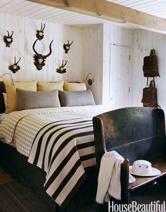 A guest bedroom merges American country with a sporty European spirit in an Aspen condo by designer Cheryl Tague. The Austrian trophies and backpacks, Welsh blanket, and English settee are antiques. The duvet cover is Medium Check by Chelsea Textiles. Walls are knotty Canadian pine with a milk-paint wash; the ceiling is painted Farrow & Ball's Clunch.