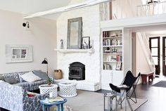 Amy painted the living area's stone fireplace—including its wood shelf—with Benjamin Moore's White Dove. An ikat-print sofa purchased at Jayson Home & Garden, coffee table from Anthropologie, and an antique mirror decorate the space.   - CountryLiving.com