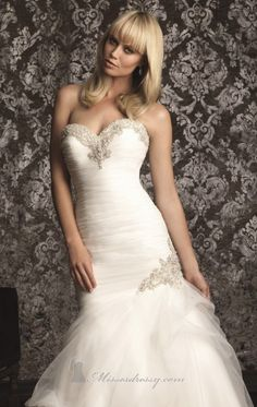 Dress elegant and romantic on your day to remember in 9002 by Allure Bridals. This refined wedding gown showcases a striking neckline with strapless top, whilst crystals and embroidery outlined the bust. The body skimming gown has soft English net, delicately ruching throughout.