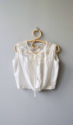 Antique 1910s Edwardian corset cover/camisole in white cotton with lovely tatted lace neckline, drawn ribbon, front button and banded waist. --- M E A S U R E M E N T S --- fits like: large bust: best fit up to 44 waist: 32 length: 17 brand/maker: n/a condition: excellent ➸ More tops & sweaters https://www.etsy.com/shop/DearGoldenVintage?section_id=5800171 ➸ Visit the shop http://www.DearGolden.etsy.com _____________________ ➸ instagra...
