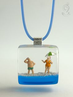 Summer breeze – summerlike beach figure pendant with mini figures, sunshade and sand on a light blue ground made of resin for the holiday feeling   ///// © Isabell Kiefhaber www.geschmeideunterteck.de
