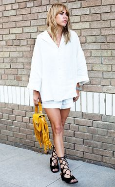 Blogger Courtney Trop of Always Judging wears an oversized white button-down blouse, shorts, lace-up sandals, and a mini yellow fringed bag