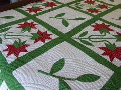 This is a pieced and applique quilt. It is hand quilted at 6-7 spi. The pattern also might be considered a Carolina Lily. So unusual is in the alternate blocks a stem and leaves appliqued. Wondered if the maker just didn't want a plain block and decided to put in that extra.Heavy quilting done in the Baptist fan style. Set in blocks with a green sashing. The separate green binding is stitched on by hand. There's an initial E stitched on the backside, but no other information to add…