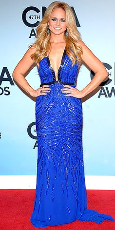 Looking svelte and sassy (just check out that plunging neckline), the Female Vocalist of the Year nominee (and Mrs. Blake Shelton) goes for all-out glam in a beaded blue gown, matching drop earrings and some major hair. http://www.people.com/people/package/gallery/0,,20316530_20753150,00.html#30048365