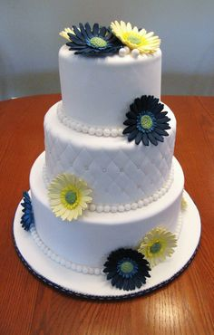 Gerbera daisy wedding cake - Navy blue and pale yellow sugarpaste gerbera daisies to match the brides flowers. Handmade sugar pearls and quilting on the middle tier.