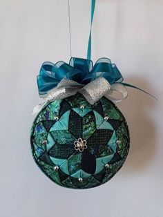 Turquoise, blues and greens in a twisted quilt pattern. Embellished with silver beads and 2 colors of ribbon. May be ordered with an I love quilting charm. Diy Quilted Christmas Ornaments, Folded Fabric Ornaments, Handmade Christmas, Christmas Tree Decorations, Christmas Tree Ornaments, Christmas Crafts, Christmas Favors, Diy Ornaments, Christmas Things