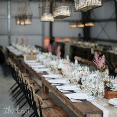 Crisp white place settings gave the wood farm tables, accented with white and burlap layered runners, a clean look #theknot