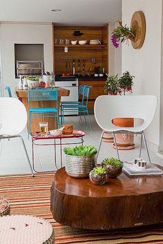 A varanda e a cozinha externa, com jeito de casa, são alegres e despojadas. A mesa é de madeira sustentável e as cadeiras Spaghetti são do designer Fernando Jaeger. De cumaru, a marcenaria foi desenhada pela arquiteta Tininha Loureiro