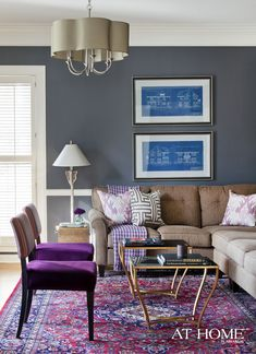 Layers of purple contrast with understated gray walls (Sherwin-Williams' Peppercorn) in the family room. Chairs, a purple houndstooth throw and gilt tables are from Mertinsdyke Home; the sectional is from La-Z-Boy, the light fixture is from Arteriors Home and the rug is from Hadidi Oriental Rug Co., Inc. On the wall, Brooks displays the home's original 1939 blueprints.