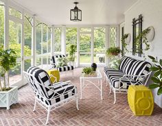Brown Jordan furnishings dressed in classic stripes from Sunbrella bring the light-filled sun porch to life; the Perennials black cushions and pillows are covered in Peter Dunham Textiles, and the citron garden stools from Emissary | archdigest.com