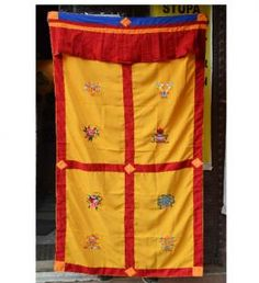 """Eight Tibetan luck bringing auspicious symbols are embroidered on the Yellow background of this door hanging. These auspicious symbols bring good health, long life and prosperity. This welcome door hanging has three loops on its topside for hanging it. Buddhist Auspicious Symbols: known as """"The Eight Jewels"""" they are represented by the?2 Golden Fish, Conch, Banner, Knot, Vase,Wheel, Lotus and Parasol and embroidered on to the door curtains ."""