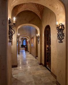 Love Hallway  AZ Custom Homes..Calvis Wyant Love the wall lighting, archways, and baseboards.