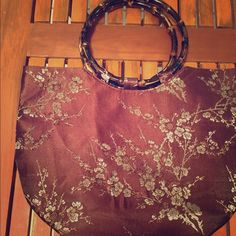 Burgundy Floral Hobo Bag Pre-loved. Hobo type bag. NO tears, no stains, no fabric pilling. As you can see in pictures the inside is like new and so is the outside. Wooden type handles. It kind of has an Asian style to it. Has a zipper although when I bought it I didn't realize it has a minor fault; you have to be gentle when opening and closing so that it doesn't get stuck. Other than that issue the hand purse is great and cute! Dimensions are: 13 in Lx 9.5 in Hx 5 in W. It's pretty roomy…