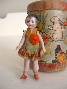 This is a precious all bisque doll with jointed arms and legs; -- marked made in Germany on back, about 3 tall, wearing felt shorts and floral top. Shes leaning against a toy also for sale in my shop.  Clothes are in good antique condition with fraying and some discoloration.  Her bisque is in very good condition but she needs a bath. I add new dolls weekly!   Thanks for looking
