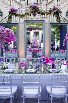 Three large mirrors back the head table, showing off the purple cake and dramatic floral arrangements.