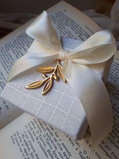 Μοντέρνες μπομπονιέρες γάμου κλαδί ελιάς χρυσό,κρεμασμένο πάνω σε κουτί δεμένο με ιβουαρ σατέν κορδελα! Καλεστε 2105157506