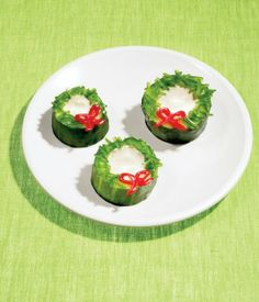 "A healthy and kid-friendly Christmas treat! Cut a cucumber into thick slices and use a teaspoon to scoop a bowl out of the center. Fill it with low-fat ranch dressing, and then use the dressing as ""glue"" to add finely chopped green bell peppers and a red bell pepper bow. Mmmmm"