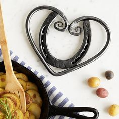 This rustic trivet features an upcycled horseshoe embraced by a swirling heart of hand-hammered steel.
