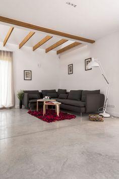 Betonowa podłoga Ultima Baufloor® w salonie. Odsłonięty fragment drewnianej konstrukcji stropu.