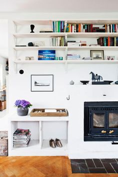 50-TᎯℒSℋUS OℳᎶℐVℰT ᎯᏉ ℬℰTᎯNDℰ ℱÅℛ: Vardagsrummets ena vägg är klädd med hyllor, från Ikea. Kaminen har placerats i en modifierad öppen spis, från Stovax, hos Narvells.