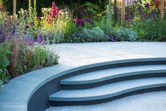 Curved limestone steps wrap around a relaxed seating area to form a bench backed by a border full of colourful planting Landscape Design, Garden Design, Tom Simpson, Timber Posts, Rhs Hampton Court, Cancer Research Uk, Polished Concrete, Water Garden, Hedges