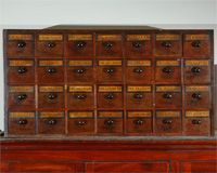 An English Apothecary Wall Chest with Hand Written Labels, to Hang or Place on Stand, Circa 1820. The narrow rectangular body holds twenty-eight square drawers with wooden knob handles.