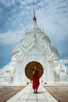 Young Buddhist monk standing in front of religious temple. Myanmar