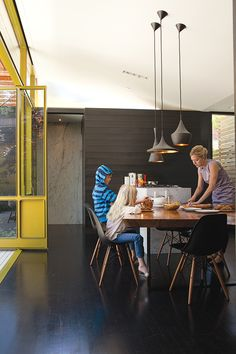walnut table...tom dixon lamps...my dream eames shell chairs...marble back wall...yellow powder coated swinging walls...DREAMY
