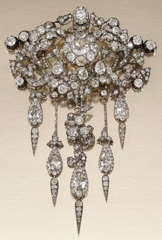 AN ANTIQUE DIAMOND DEVANT DE CORSAGE, 1860s. Of foliate design, centring on a diamond cluster within an openwork surround of acanthus and ivy leaves, suspending five articulated pendant drops, set with cushion-, pear-shaped, circular- and rose-cut diamonds, further embellished with cushion-shaped and circular-cut stones in cut-down collets. #antique #DevantDeCorsage
