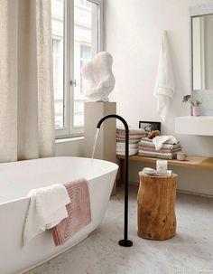 Une salle de bains design avec sol en marbre et baignoire îlot. Mariage du carrelage marbre, de la baignoire en porcelaine et des rideaux en lin. #salledebain #marbre #baignoire #design