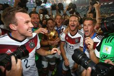 RIO DE JANEIRO, BRAZIL - JULY 13: Mesut Oezil of Germany holds the World Cup trophy while celebrating with teammates Kevin Grosskreutz, Roman Weidenfeller, Matthias Ginter, Shkodran Mustafi and Erik Durm of Germany after defeating Argentina 1-0 during the 2014 FIFA World Cup Brazil Final match between Germany and Argentina at Maracana on July 13, 2014 in Rio de Janeiro, Brazil. (Photo by Julian Finney/Getty Images)