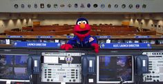 Sesame Street's Elmo leans over the console at the Mission Control Center in Florida