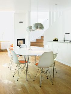 The kitchen in this charming prefab house outside of Stockholm is all about modernist classics. A Splügen Bräu pendant lamps for Flos hang over a Super-Elliptical table by Piet Hein and Bruno Mathsson for Fritz Hansen. Photo by Annika Lundvall - See more at: http://www.dwell.com/houses-we-love/article/clean-slate-celebrating-simplicity-scandinavian-interior-design#4Swedish Prefab Home, Dining Room