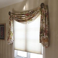 Scarf swags in a multi colored floral, embellished with a tassel trim decorate side by side windows in an upstairs hallway.  Hunter Douglas honeycomb shades protect a large painting on the stairwell from UV rays.  Valances made by Curtain Call.