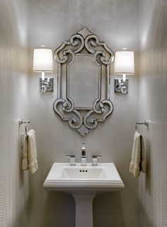 This jewel of a Powder Room was created by Design Connection, Inc. using a unique light reflective Silver Metallic Snakeskin Wallpaper.  A Crystal Ceiling Light Fixture & Crystal Sconces With Drum Shades accent this small but dramatic Powder Room. Bathrooms By Design Connection, Inc. | Kansas City Interior Design http://designconnectioninc.com/ #PowderRoom #HalfBath #InteriorDesign