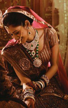A Marwadi bride looking graceful in a kundan necklace, Emerald Rani haar, earrings, rings, borla (head accessories), naths (nose ring), chudis and kangans (bangles).