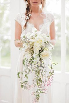 bohemian wedding bouquets bride with flowers in her hair holds a cascade boho bouquet with white roses and greens sarah gawler