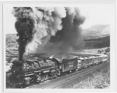 This black and white photograph shows the Atchison, Topeka & Santa Fe Railway Company's steam locomotive 5000, 2-10-4, helping the 13 D.E.P. take the eastbound Super Chief up Raton Pass below Wooten, Colorado.  Creator: Atchison, Topeka, and Santa Fe Railway Company Date: Between 1930s and 1940s
