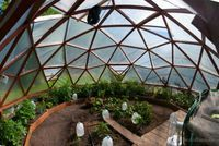 Geodesic Dome Greenhouse - milk jugs right next to the plants in the spring to pick up heat during the day and a garden hose from the water pump around the outside of the greenhouse, right next to the plants. The hose is much warmer than the air at night.