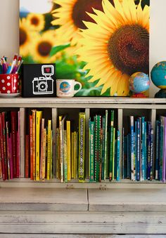 Love it.  Love the bright happy colors.  Love the books organized by rainbow color.  Love the polka dot cup.  Love the globes.  ♥ So doing this to H's playroom bookshelf.