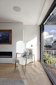 Neben der massiven Glas-Schiebetür sehen wir eines von vielen Beispielen von elegant gestalteten, neutrale getönten Möbel im Haus. Dieser Sessel verfügt über eine minimalistische Holzrahmen und Schaltfläche getuftet weiße Lederpolsterung.