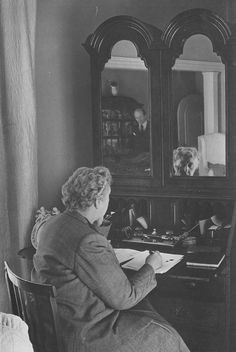 Agatha at her desk with Max looking on.
