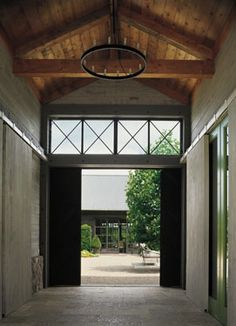 Inside barn foyer with barn doors vaulted wood ceilings and chandelier in a Northern California home. | Barbara Colvin | http://cococozy.com
